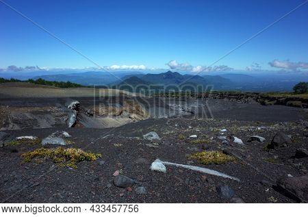 South America nature landscape, Spare vegetation on dark lifeless ash and post-eruptive ravine on mountainside of Villarrica volcano, clear blue sky, Villarrica national park in Chile