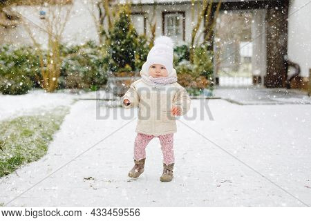 Happy Little Baby Girl Making First Steps Outdoors In Winter Through Snow. Cute Toddler Learning Wal