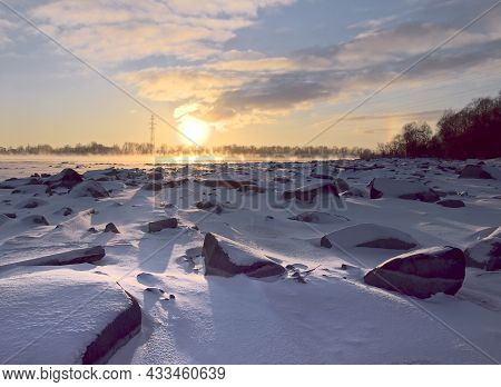 Sun Ball At Sunset. The Stone Banks Of The Ob Are Covered With Snow. Golden Blue Sky. Power Line Tow