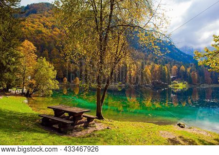 The wooden table with benches. Lake Fuzine. Yellow and orange trees are reflected in the green smooth water of the lake. Alps, Northern Italy