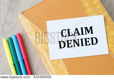 Card On A Notepad With The Text Claim Denied, Next To Colored Markers On A Wooden Background