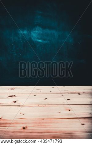 Wooden table with blackboard background