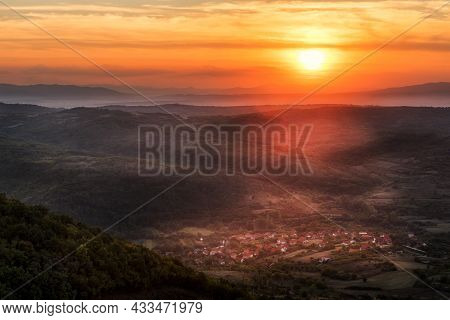 Sunset Over Small Village Between Hills And Mountains. Shades Of Mountain Layers In Sunset