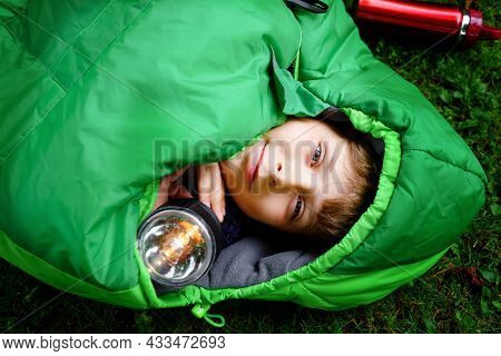 Preteen School Kid Boy In Sleeping Bag Camping. Outdoors Activity With Children In Summer. Fun And A
