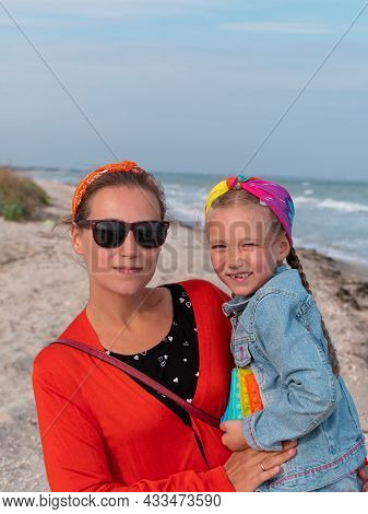 Cheerful Mother And Daughter Smiling Walking On Sea Beach. Happy Family. Cute Little Child Playing R