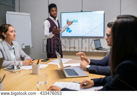 Young confident speaker or coach making report in front of audience at meeting or seminar