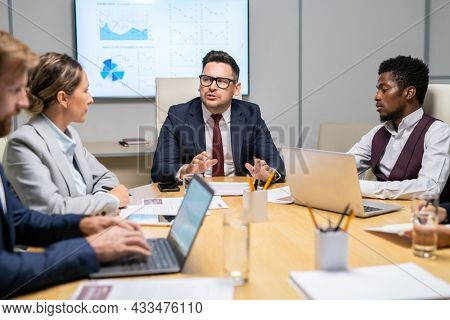 Confident coach looking at one of white collar workers during his speech at conference or training