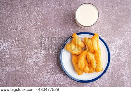 Top View Of Deep-fried Dough Sticks Or Chinese Doughnut Sticks On White Plate And A Glass Of Soybean