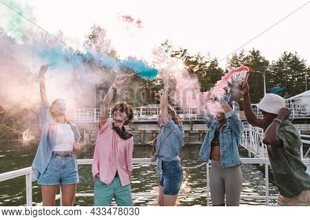 Cheerful young people in casualwear dancing with firecrackers by waterside on summer day
