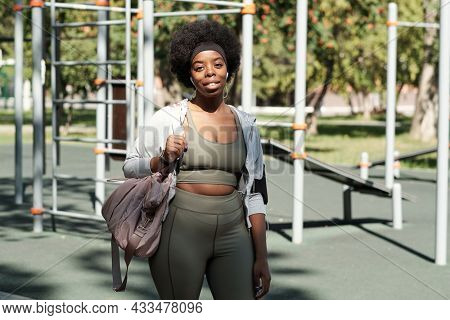 Happy young African sportswoman with handbag on shoulder standing against sports facilities