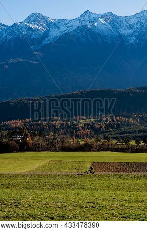 Mountain Biking Through Alpine Landscape During Autumn With Orange Colored Larch Trees And Snow Topp