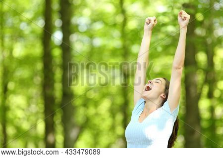 Excited Woman Raising Arms In A Green Forest On Summer Vacation