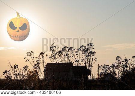 Halloween Concept. Mysterious Abandoned House At Sunset In Dark Light. Transparent Pumpkin Jack Lant