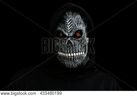Isolated Man Dressed In Death Carnival Costume On Black Background With Fire On Eyes. Halloween Holi