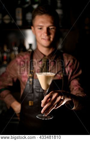 Hand Of Male Bartender Gently Holds Martini Glass With Cocktail. Blurred Bartender In Background