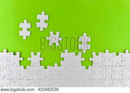 Unfinished White Puzzle Pieces On A Green Background