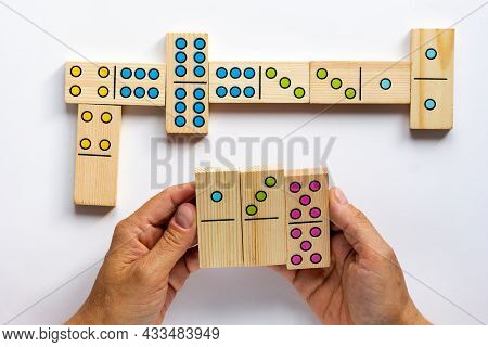 Top View Of Woman Hands Holding Wooden Dominoes Gaming Pieces On The White Background