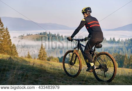Back View Of Male Cyclist In Cycling Suit Riding Bike On Road. Man Bicyclist Wearing Safety Helmet W