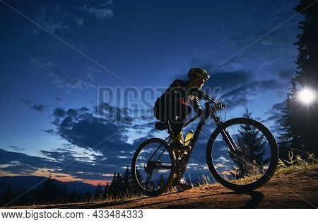Young Man Cycling Bicycle Under Beautiful Night Sky. Male Bicyclist In Safety Helmet Riding On Hills