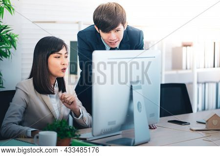At Work, A Young Attractive Woman Is Gazing At Her Computer And Conversing With A Coworker
