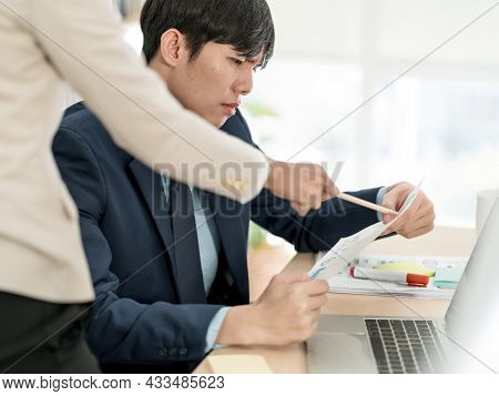 A Group Of Asian Businesspeople Are Conversing Informally. In The Office, Employees Talk About Their