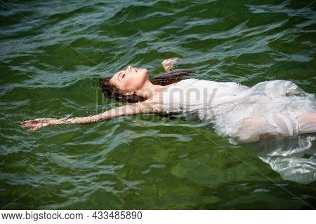 Young Sexy Woman Is Swimming In The Transparent, Blue Sea. Sensual Slim Woman Floating On The Water