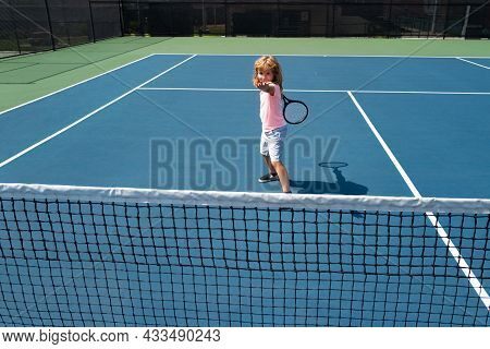 Cute Kid Boy At The Tennis Competition. Young Boy Playing Tennis At Court.