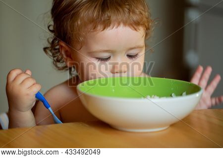 Happy Baby Eating Himself With A Spoon.