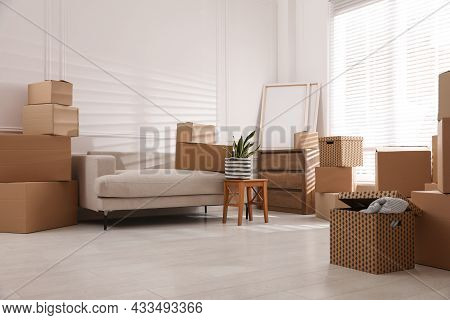 Furniture And Cardboard Boxes With Packed Stuff In Room. Moving Day