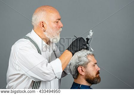 Hairdresser Making Of A Color Hair For A Bearded Hipster Guy. Professional Hairdresser Coloring Man