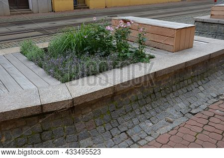 On The Edge Of The Elevated Terrace Overlooking The Park Is A Concrete Long Flowerpot With Wood Pane
