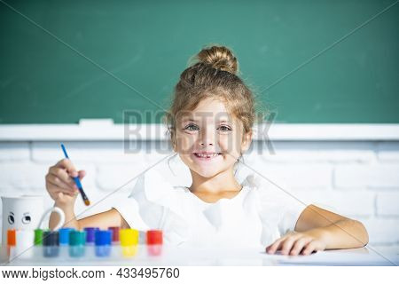 School Girl Pupil Drawing A Picture. Cute Little Preschooler Child Drawing At School.