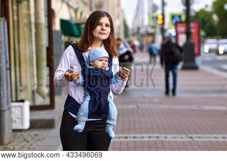 Young Woman Carries Infant In Baby Sling On Moskovsky Prospekt In St Petersburg Russia.