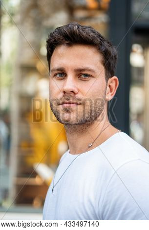 Handsome Young Male With Stylish Haircut And Bristle Wearing White T Shirt Looking At Camera While S