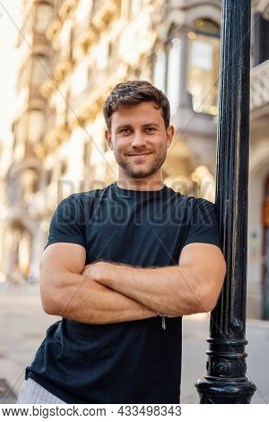 Confident Handsome Young Unshaven Guy In Casual T Shirt With Arms Crossed Leaning On Street Pole And