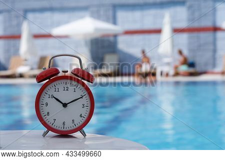 Red Analog Alarm Clock With Blurred Background Of Relaxation Pool
