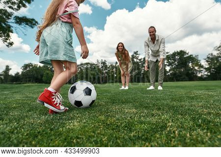 Closeup Of Little Girl Kicking The Ball While Parents Watching. Young Family Playing Football On The