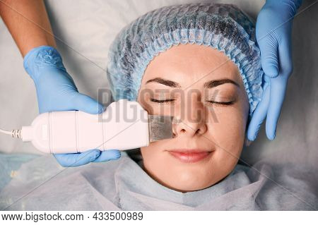 Close Up Of Beautician Hands Using Ultrasonic Scrubber While Cleaning Female Client Face. Woman In D