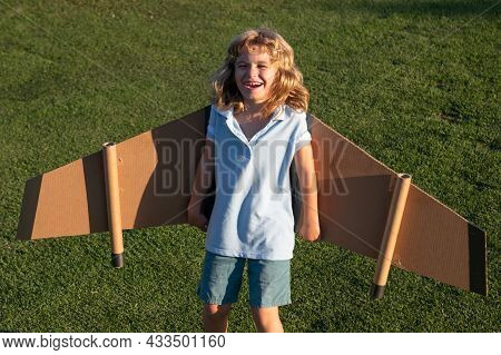 Smiling Child Flying In Plane Made Craft Of Cardboard Wings. Dream, Imagination, Happy Childhood. Tr