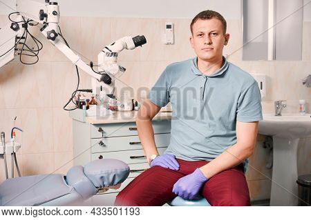 Portrait Of Dentist In Sterile Gloves Looking At Camera. Male Stomatologist Sitting Near Dental Micr