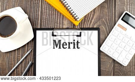 Merit Text On Paper With Coffee, Calculator And Notebook. Business