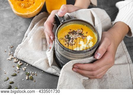 Hands Are Holding A Cup Of Homemade Pumpkin Soup With Seeds, Sesame Seeds And Flax Seeds Close-up, W