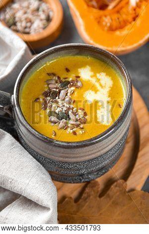 Cup Of Homemade Pumpkin Soup With Seeds, Sesame Seeds And Flax Seeds Close-up, Warm Autumn Food Vert