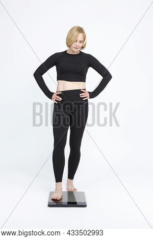 Body Weight Ideas. Mature Caucasian Woman Checking Her Weight With Floorstanding Weigh-scales.
