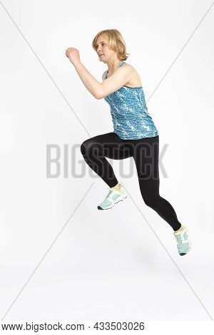 Professional Mature Female Runner In High Jump Against White Background.