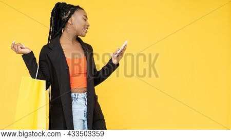 Online Shopping. Sale Banner. Black Friday. Cheerful Afro Woman With Shopper Bag Paying Order On Pho