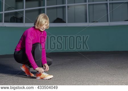Sport Ideas. Active Female Runner Tighten Up Her Shoelaces During Jogging Training Exercise Outdoor.