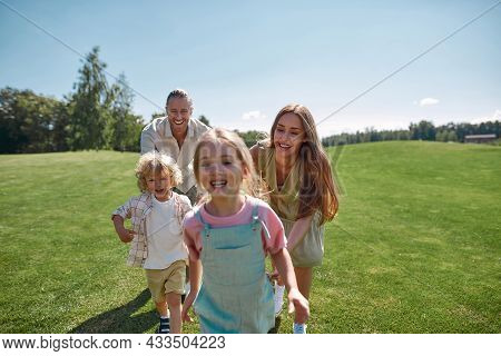 Joyful Young Parents Having Fun Together With Two Little Children, Boy And Girl In Green Park On A S