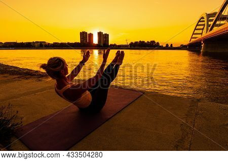 Woman Exercising Pilates On Sunny Day. Teaser Exercise.