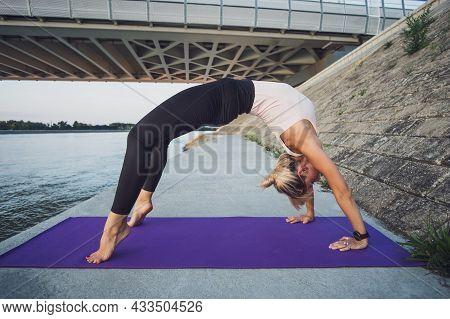 Young Woman Is Exercising Outdoor. She Is Practicing Yoga. Urdhva Dhanurasana / Bridge Pose.